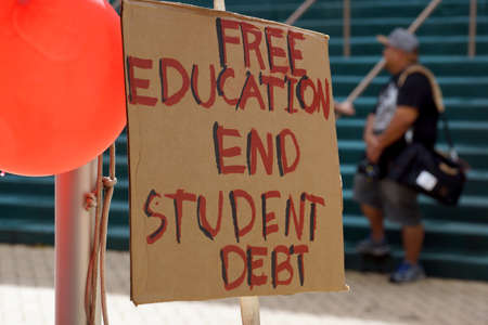 Honolulu - November 12, 2015:  Free Education End Student Debt Sign on the Campus of the University of Hawaii Manoa next to red balloons during protest of the cost of college. 新聞圖片