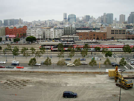 San Francisco - September 9, 2007: Densification CAT Bulldozer makes holes in the ground at construction site, Caltrain Station, and San Francisco Cityscape in the distance. Editorial