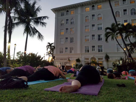 Waikiki - September 19, 2017: Large group of People do Pidgin yoga pose at Vino and Vinyasa event hosted by the Moana Hotel in Honolulu, Hawaii.