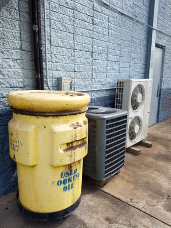 Honolulu - September 19, 2016:  Yellow Tank of Used Cooking Oil, to be turned to Biodiesel, and Air Conditioning units outside of restaurant on Oahu, Hawaii.