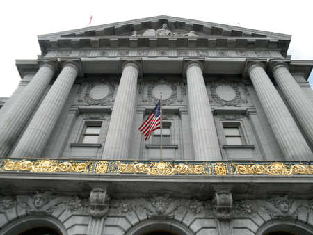 San Francisco - August 10, 2010: Looking up at City Hall with USA flag waving on a foggy day.  San Francisco City Hall is the seat of government for the City and County of San Francisco, California. Editöryel