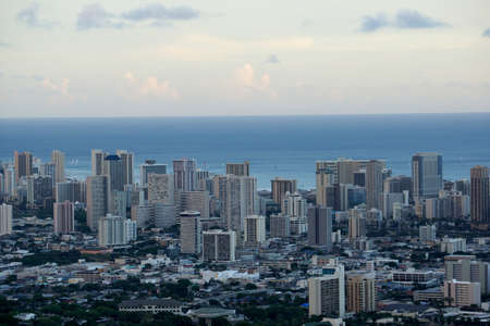 Aerial of Honolulu, Waikiki, Buildings, parks, hotels and Condos with Pacific Ocean stretching into the distance on nice day.