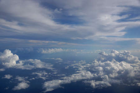 Aerial of Fluffy Clouds in a blue sky between islands of Hawaii.