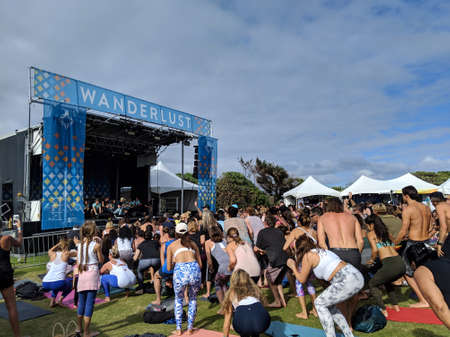 North Shore, Oahu - March 3, 2019: People bend down to jump up at Wanderlust MC Yogi Yoga Class at outdoor yoga class facing stage at Wanderlust yoga event.
