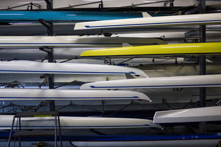 Stacks Of Gleaming White Crew Rowing Shells In A Boathouse