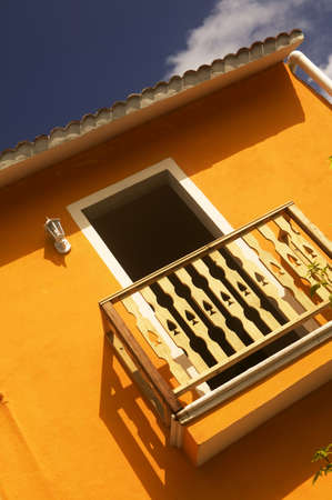 An orange wall and small balcony with wooden railing basks in the afternoon sun on Isla Mujeres, Mexico Stock Photo