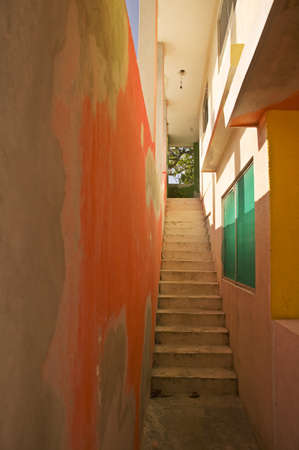 second floor: Stairs go past an orange wall and green shutters to a second floor on Isla Mujeres Stock Photo