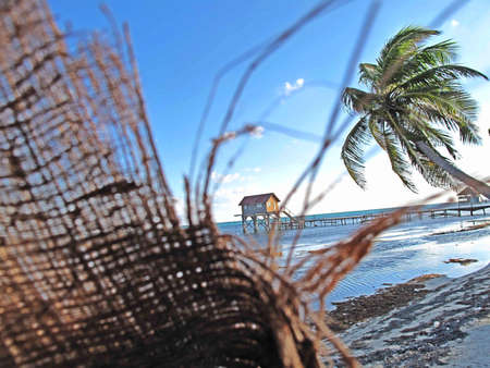 A ripped, coconut-fiber matt blows in the wind on the beach. Stock Photo