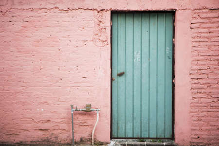 Teal Wooden Door and Pink Wall Stock Photo