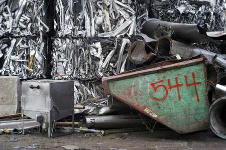 reusing: Green Dumpster and Aluminum Bales Stock Photo
