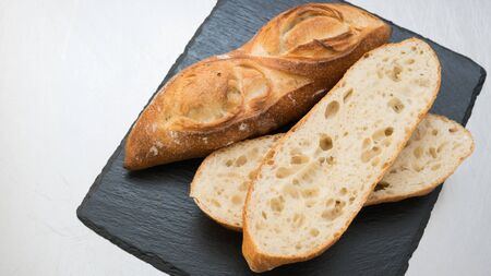 sliced bread: Bageutte and sliced bread on black slate Stock Photo