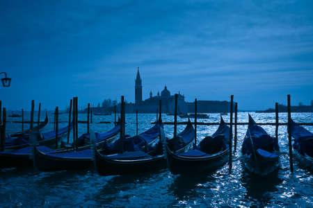 Gondolas moored by Saint Marks square with San Giorgio di Maggiore church in the background - Venice, Venezia, Italy, Europe photo