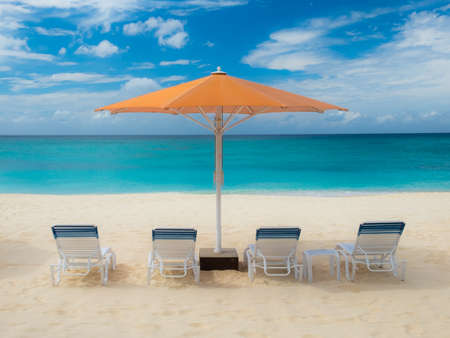 Parasol and Sun loungers on Seven Mile Beach by the Caribbean sea, Grand Cayman Stock Photo