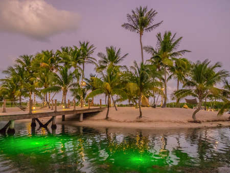 Wooden bridge leading to a man made sandy tropical island at dusk illuminated by lanterns and strip light on palm tree at Camana Bay, Grand Cayman