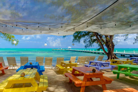View of the Caribbean sea and a jetty from the beach with sun loungers and colorful table, Grand Cayman