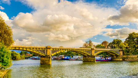 Boats moored by Twickenham Bridge spanning over the river Thames, London U.K