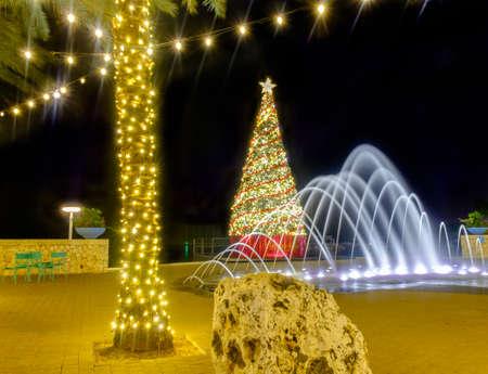 Christmas tree, water fountain, illuminated palm tree with strip lights on a pedestrian street of Camana Bay Grand Cayman, Cayman Islands, Dec 2017