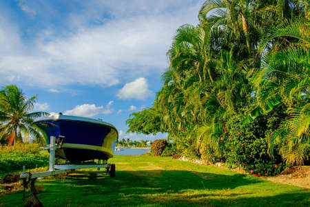 Trailer and a boat on a lawn by a tall tropical vegetation wall near the water, Grand Cayman, Cayman Islands Stock Photo