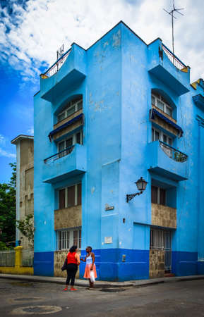 Havana, Cuba, July 2019, two women talking outside a blue building in Calle Muralla in the oldest part of the city 스톡 콘텐츠