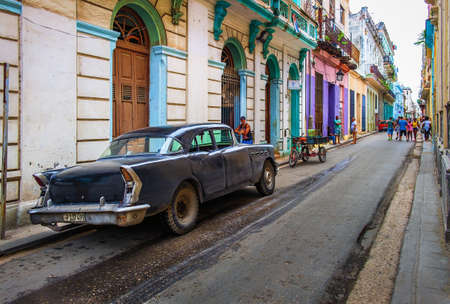 Havana, Cuba, July 2019, urban scene in the oldest part of the city with a black American 1950's car parked in Calle Cuba