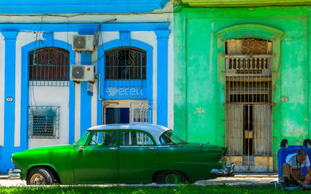 Havana, Cuba, July 2019, view of an old American car parked in front of two colorful buildings in Calle San Juan de Dios in the old part of the city Archivio Fotografico