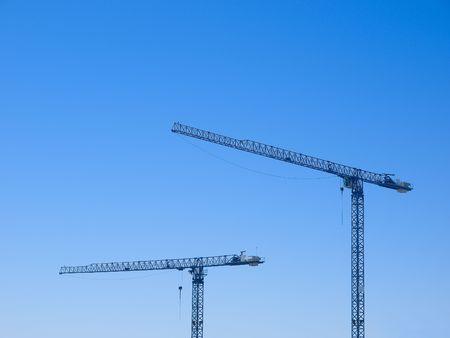 heavy construction: Two crane isolated on blue sky Stock Photo