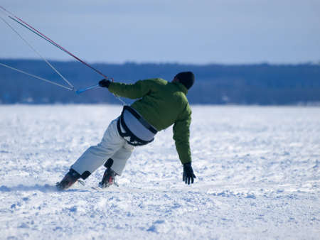 kiting: Men ski kiting on a frozen lake