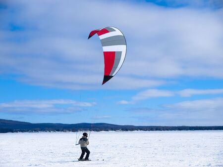 kiting: Men ski kiting on a frozen lake