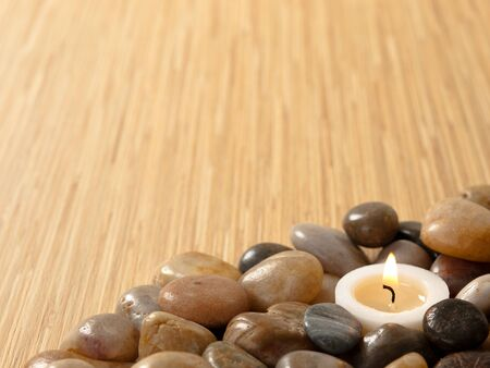 candle: Zen candle in pebbles with wood background Stock Photo