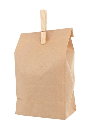 Old-fashied lunch bag with wooden clothes pin on white background photo
