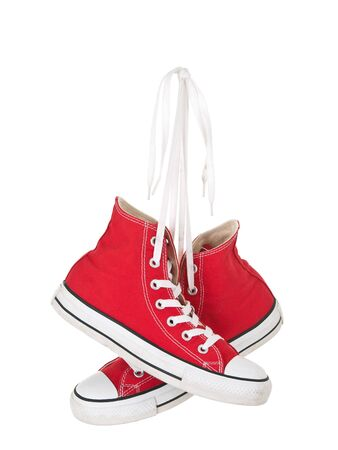 Vintage hanging red shoes tied on pure white background Stock Photo
