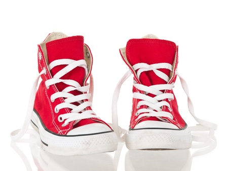 Red vintage canvas sneakers untied on white background 版權商用圖片