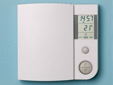 Electronic programmable thermostat on blue wall 版權商用圖片
