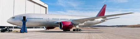 Big passenger  airplane red and white parked near hangar