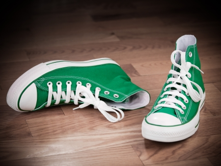 Retro green sneakers left on wooden floor grungy effects Фото со стока