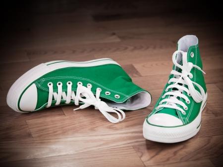 untied: Zapatillas verdes retro dejaron en efectos grungy de piso de madera
