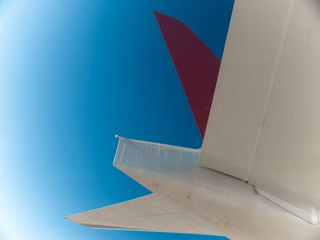 Airplane red tail with stabilizers details on blue sky