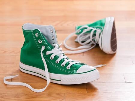Retro green sneakers left on wooden floor photo