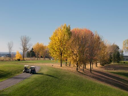 Golf in fall with men driving carts to the fairway photo