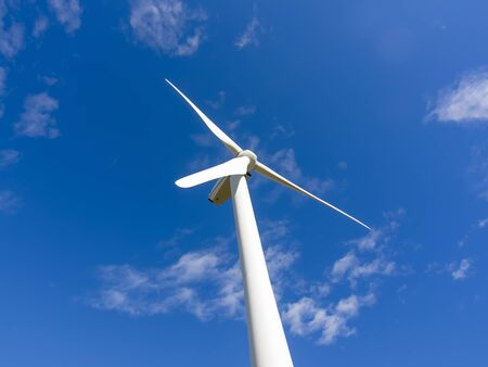 stopped: Single wind turbine stopped in blue sky Stock Photo