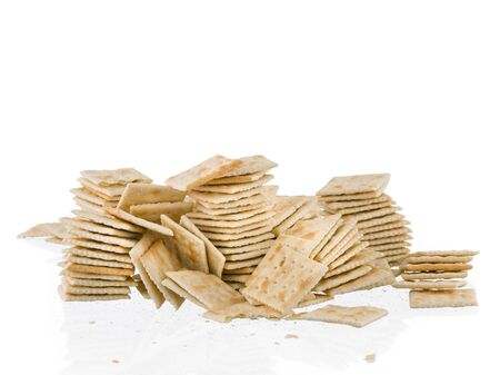 mess: Soda crackers stacks fallen mess isolated on white background Stock Photo