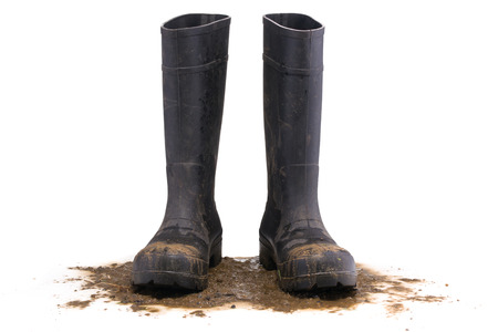泥だらけのゴム製ブーツ正面の白い背景で隔離