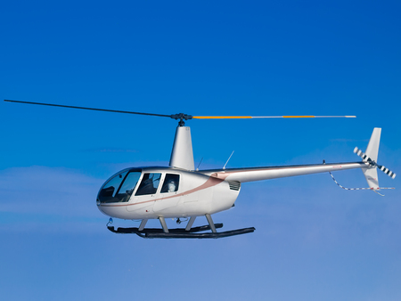 Helicopter flying in blue sky side view Stockfoto