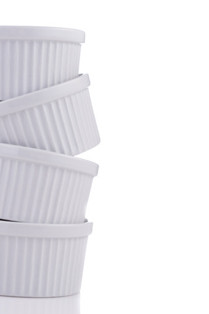 unsound: White ramekin dishes very unstable stack close-up isolated on white background