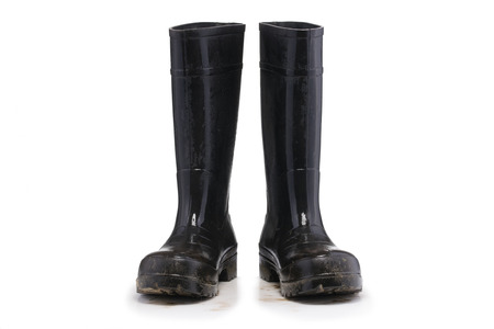 masculin: Wet dirty Mud boots isolated on pure white background front view