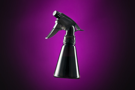 Black mini spray bottle isolated on purple and black background