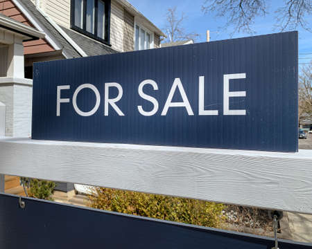 "A real estate, ""for sale"" sign is displayed in front a home in a residential neighbourhood."