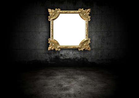Golden frame in a dark room Stock Photo