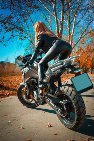 Attractive young woman in black leather outfit with classic style motorcycle.