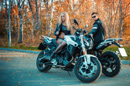 An attractive guy and a young woman in a black leather outfit with a motorcycle.